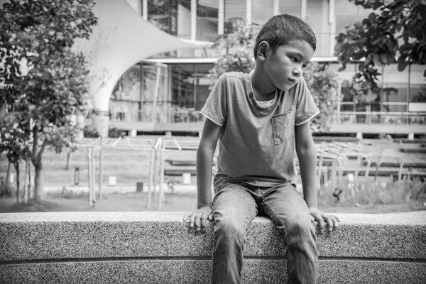Child sitting on stone wall looking sad