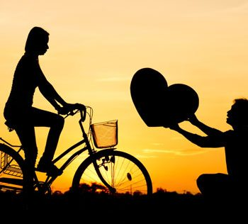 man presenting woman on a bike a large heart
