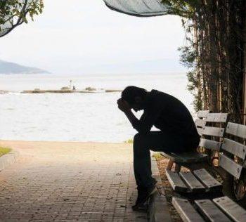 man sitting on bench looking sad